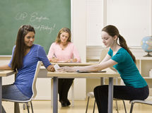 Students passing notes in classroom Royalty Free Stock Photo