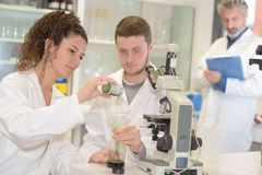 Students performing science experiment under observation. Science Royalty Free Stock Images