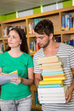 Students with pile of books in the library Stock Images