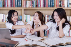 Students pile up their hands in library Royalty Free Stock Photo