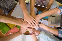 Students placing hands together over library table Stock Images