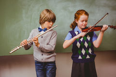 Students playing flute and violin in classroom. Portrait of cute little students playing flute and violin in classroom Stock Photo