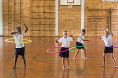 Students playing with hula hoop in school gym Stock Images