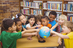 Students pointing at a globe Royalty Free Stock Photo