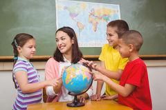 Students pointing to places on a globe Stock Images