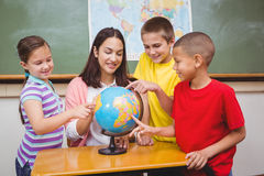 Students pointing to places on a globe Royalty Free Stock Image