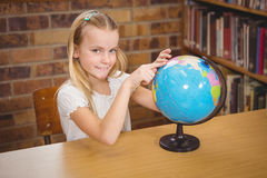 Students pointing to places on a globe Stock Photography