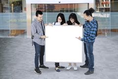 Students pointing on white board with copy space. Group of college students pointing on white board with copy space Stock Photos