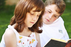 Students.Portrait de los libros de lectura lindos de los niños en natural rodean Foto de archivo