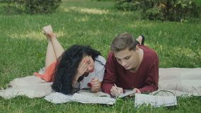 Students prepares to exams in park, guy writes some information in notebook stock footage