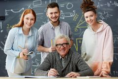 Students and professor. Happy professor and his successful students looking at camera on background of blackboard in classroom royalty free stock image