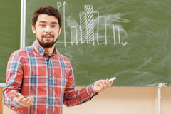 Students put graphs on a blackboard. College classes. Young agitated male student standing on the background of a chalkboard with graph on it Royalty Free Stock Images