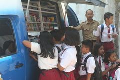 Students queuing up to read a book in the mobile library Royalty Free Stock Photography