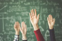 Students raised up hands green chalk board in classroom stock photos