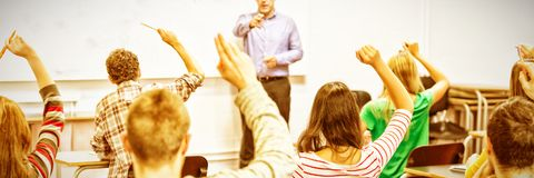 Students raising hands in classroom. Rear view of students with hands raised with teacher in classroom stock images