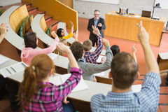 Students raising hands with teacher in the lecture hall. Rear view of students raising hands with a teacher in the college lecture hall Stock Photo