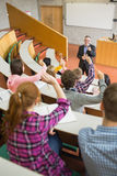 Students raising hands with a teacher in the lecture hall Stock Photography