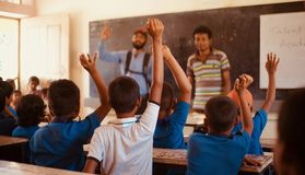 Students raising their hands in a classroom. Isolated unique photo royalty free stock image