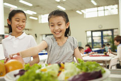Students reaching for healthy food in school cafeteria royalty free stock image
