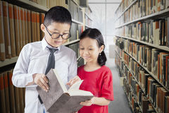 Students read books in library aisle. Portrait of two elementary school students reading a book together while standing in the library aisle Stock Photography