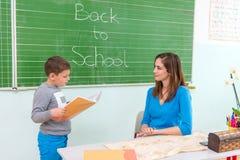 Students read a woman teacher at the blackboard Stock Photos
