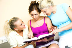 Students reading a book. Portrait of three pretty students sitting on the bed and reading a book Royalty Free Stock Images