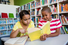 Students reading book against bookshelf at library in school Stock Image