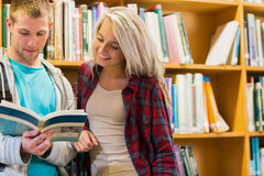 Students reading book against bookshelves in library Royalty Free Stock Photos
