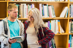 Students reading book against bookshelves in library Stock Photo