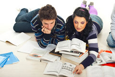 Students reading a book on floor. Two students learning and reading a book together on wooden floor Royalty Free Stock Images