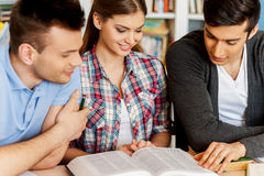 Students reading book in library. Three cheerful students reading a book together while sitting against bookshelf in a library Royalty Free Stock Photography