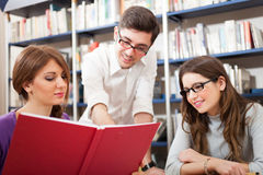 Students reading a book in a library. Students reading a book together Stock Photo