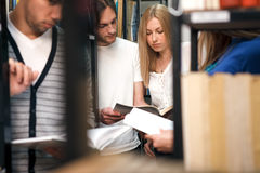 Students reading book in library. Young students reading book in college library Stock Image