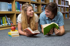 Students reading book lying on library floor Stock Photography