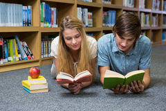 Students reading book lying on library floor Royalty Free Stock Photo