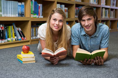 Students reading book lying on library floor Royalty Free Stock Images