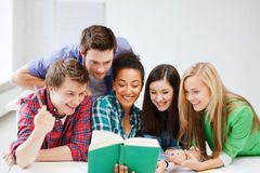 Students reading book at school. Education concept - students reading book at school Royalty Free Stock Photography