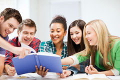 Students reading book at school. Education concept - group of students reading book at school Royalty Free Stock Photography