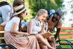 Students reading book while sitting on bench together in park Stock Image