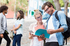 Students reading book. While their friends interacting in the background Stock Image