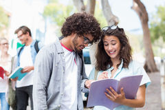 Students reading book. While their friends interacting in the background Royalty Free Stock Photo