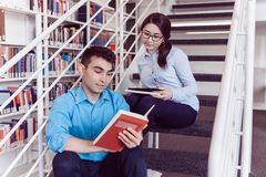 Students reading book together in the library Royalty Free Stock Image