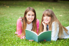 Students reading a book. Two beautiful students reading a book on the grass Stock Images