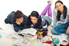 Students reading books  home. Two students reading a book while their colleague smiling for camera and together doing homework Stock Photos