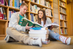 Students reading books on library floor. Two young students reading books against bookshelf while sitting on the library floor Royalty Free Stock Photos