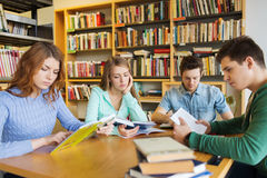 Students reading books in library. People, knowledge, education, literature and school concept - students reading books and preparing to exams in library Stock Image