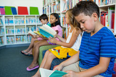 Students reading books while sitting on seats at school library Stock Photo