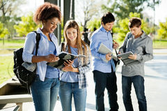 Students Reading Books In University Campus Stock Photos