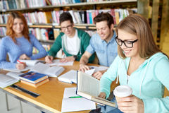 Students reading and drinking coffee in library Royalty Free Stock Photo