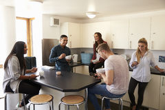 Students Relaxing In Kitchen Of Shared Accommodation stock photography